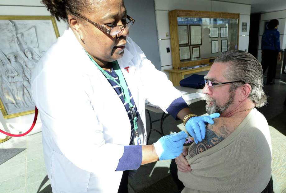 A nurse administers an influenza vaccine earlier this year. Photo: Matthew Brown / Hearst Connecticut Media / Stamford Advocate