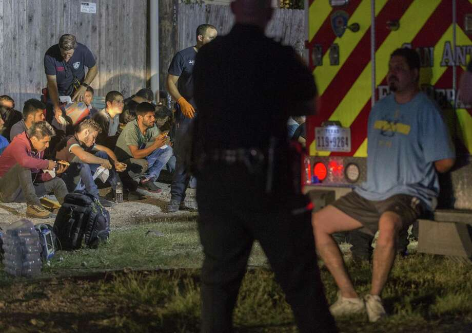 Gerardo Carreon, in handcuffs, sits on the back step of an ambulance on June 12 near Loop 410 and Broadway where a group of undocumented immigrants sought to escape when the tractor-trailer rig Carreon was driving was approached by law enforcement. Several immigrants were injured as they ran. Carreon was sentenced Thursday to 5 years and 10 months in federal prison on a charge of conspiracy to transport undocumented immigrants. Photo: William Luther /San Antonio Express-News / © 2018 San Antonio Express-News
