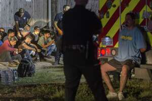 Gerardo Carreon, in handcuffs, sits on the back step of an ambulance on June 12 near Loop 410 and Broadway where a group of undocumented immigrants sought to escape when the tractor-trailer rig Carreon was driving was approached by law enforcement. Several immigrants were injured as they ran. Carreon was sentenced Thursday to 5 years and 10 months in federal prison on a charge of conspiracy to transport undocumented immigrants.