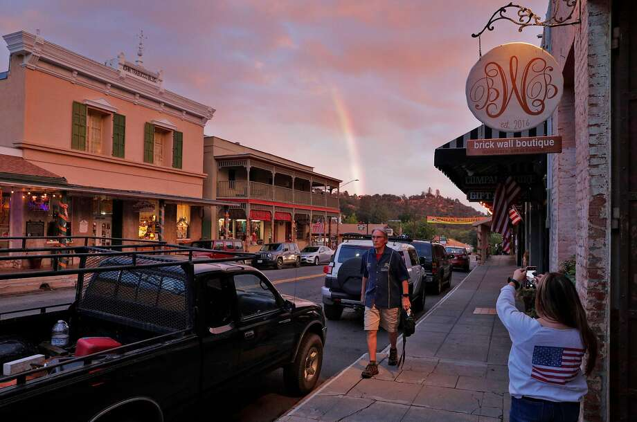 Nadean Andrade takes a photo of a rainbow in downtown Mariposa, Calif., on Wednesday, October 3, 2018. The tourist town, still reeling from the loss of business due to fires, is now also dealing with the effects of the government shutdown and having a number of its residents — many of whom work for Yosemite — not receiving pay. Photo: Carlos Avila Gonzalez / The Chronicle