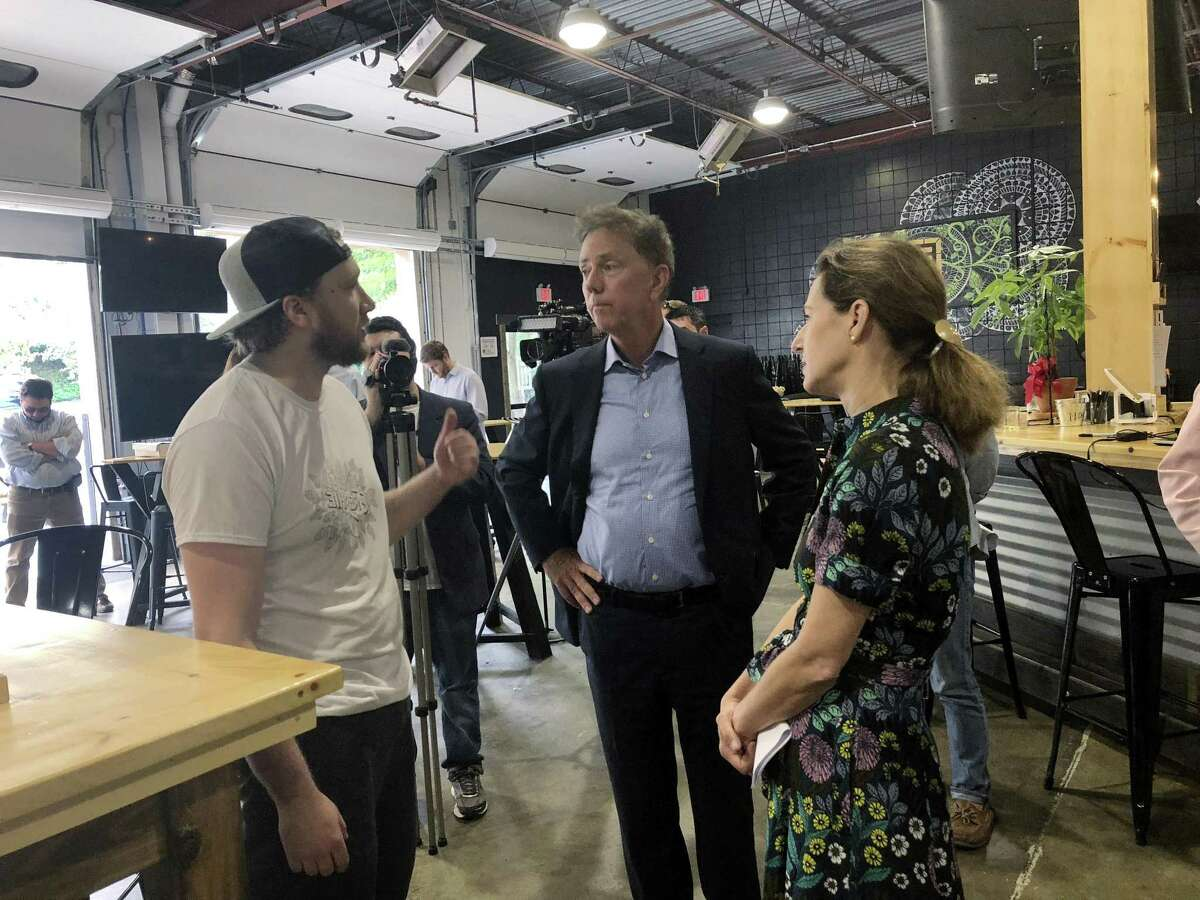 Ned Lamont, Democratic nominee for governor, and his running mate Susan Bysiewicz talk with Matt Weichner, a co-founder of Tribus Beer Co. in Milford on Thursday.