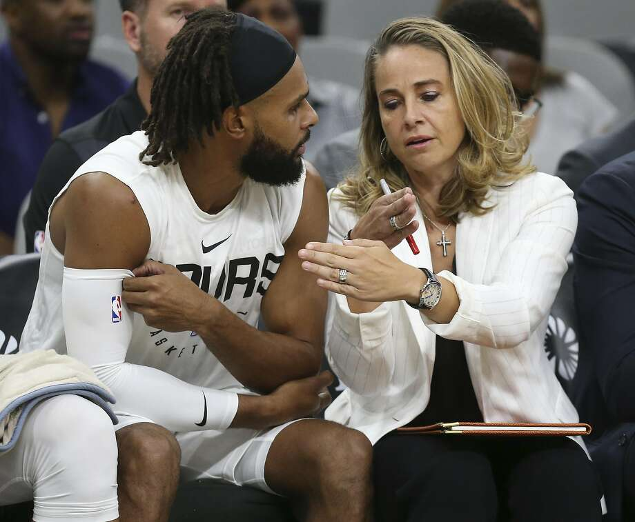 San Antonio Spurs assistant coach Becky Hammon talks with Patty Mills on the bench during the first half against the Miami Heat at the AT&T Center, Sunday, Sept. 30, 2018. Photo: Jerry Lara, San Antonio Express-News