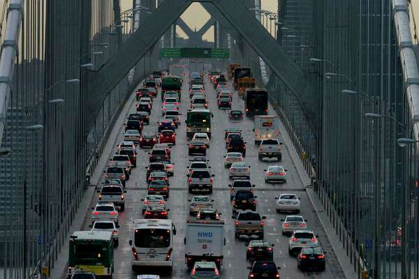 FILE - In this Dec. 10, 2015 file photo, vehicles make their way westbound on Interstate 80 across the San Francisco-Oakland Bay Bridge as seen from Treasure Island in San Francisco. California is telling automakers they must still comply with the state's strict vehicle mileage standards even if President Donald Trump rolls them back. The action Friday, Sept. 28, 2018, by the California Air Resources Board was widely expected. It sets up likely court battle if the Trump administration follows through with an attempt to revoke California's unique authority to set its own vehicle emissions standards. (AP Photo/Ben Margot, File)