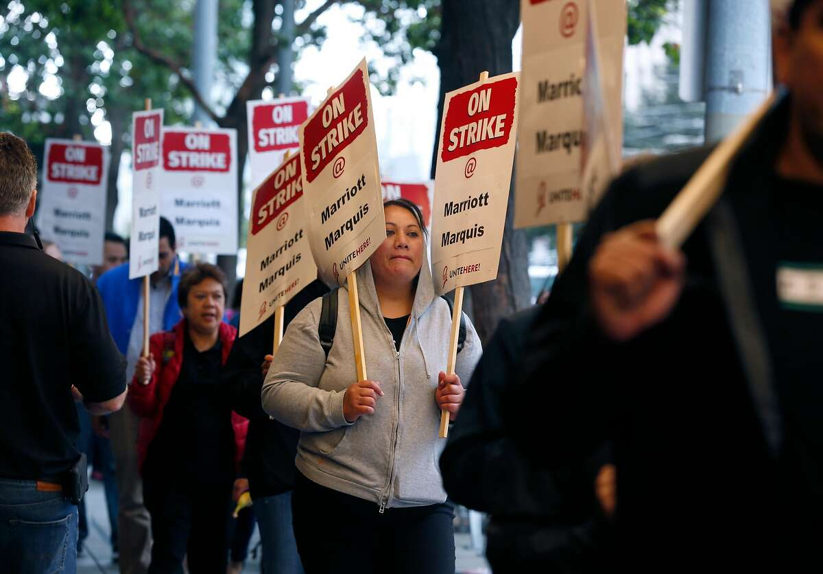 Hotel workers walk a picket line outside of the Marriott Marquis hotel at Fourth and Mission streets as thousands of workers walked off the job in a contract dispute in San Francisco, Calif. on Thursday, Oct. 4, 2018.