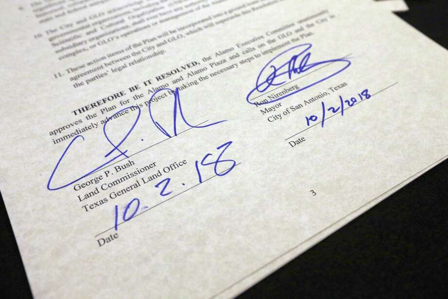 The signatures of San Antonio Mayor Ron Nirenberg and Texas Land Commissioner George P. Bush Tuesday on a copy of the Alamo Executive Committee resolution, signed moments before accepting the Alamo Master Plan general terms which include the closing of Alamo Street through Alamo Plaza and moving the cenotaph to a different location in the plaza. Photo: William Luther /San Antonio Express-News / © 2018 San Antonio Express-News