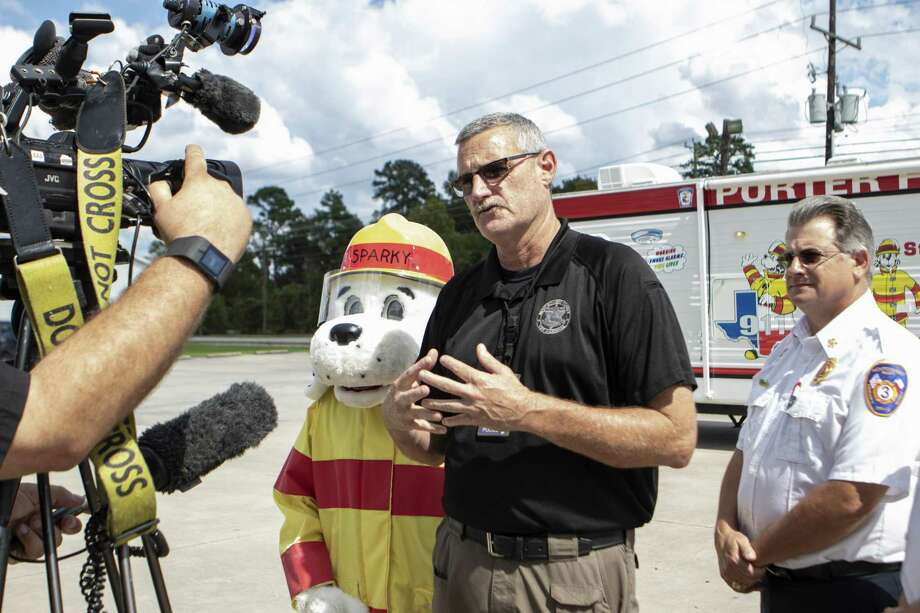 Porter Fire Department's mascot Sparky and Montgomery County Emergency Services Dispatch #3 fire chief Leonard Mikeska stand beside Montgomery County fire marshal Jimmy Williams as he speaks to the media Thursday, Oct. 4, 2018 at Porter Fire Station 121. Montgomery County fire officials announced a program to aid in educating people about the need for working smoke detectors and aiding in making homes safer against fires. Photo: Cody Bahn, Houston Chronicle / Staff Photographer / © 2018 Houston Chronicle