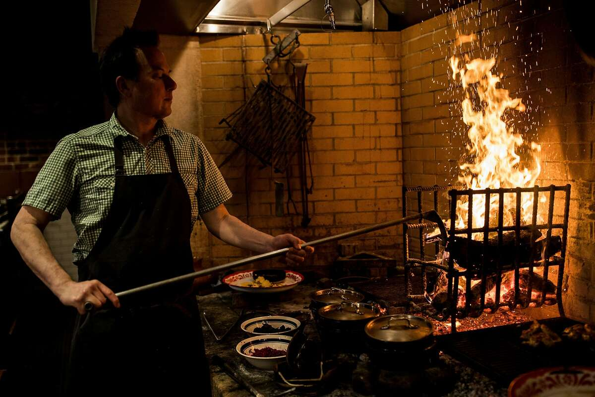 Chef Russ Moore of Camino work the wood-fired oven during dinner service in Oakland, Calif. on Monday, March 26, 2018.