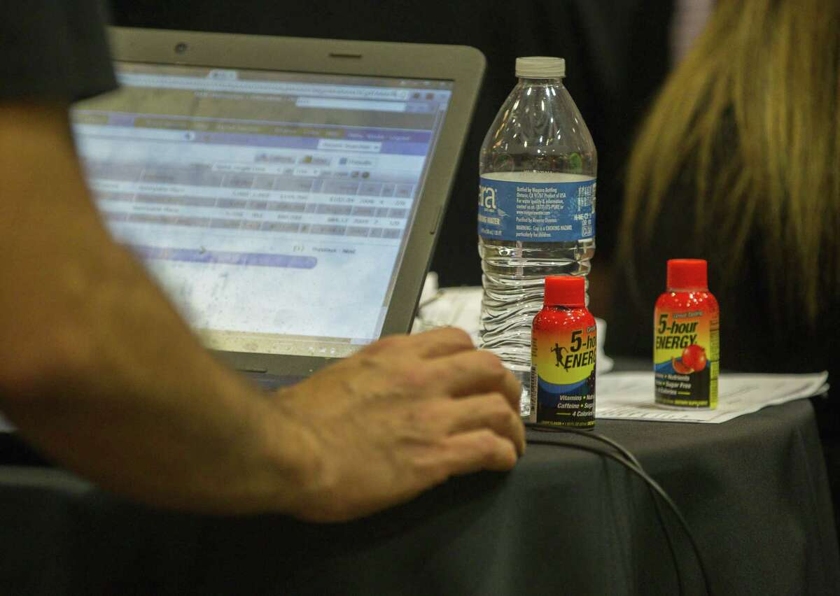 A man looks at properties on his computer during the monthly foreclosure auction hosted by Harris County at the Bayou City Events Center, Tuesday, Oct. 2, 2018 in Houston.