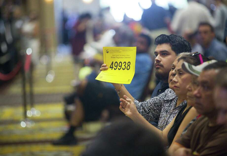 A bidder raises their number during the monthly foreclosure auction hosted by Harris County at the Bayou City Events Center, Tuesday, Oct. 2, 2018 in Houston. Delinquent tax sales are divided up by constable precincts during the monthly foreclosure auction. Photo: Mark Mulligan, Houston Chronicle / Staff Photographer / © 2018 Mark Mulligan / Houston Chronicle