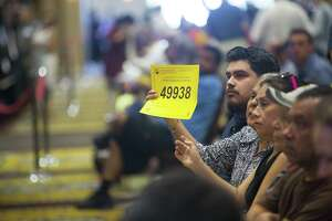 A bidder raises their number during the monthly foreclosure auction hosted by Harris County at the Bayou City Events Center, Tuesday, Oct. 2, 2018 in Houston. Delinquent tax sales are divided up by constable precincts during the monthly foreclosure auction.