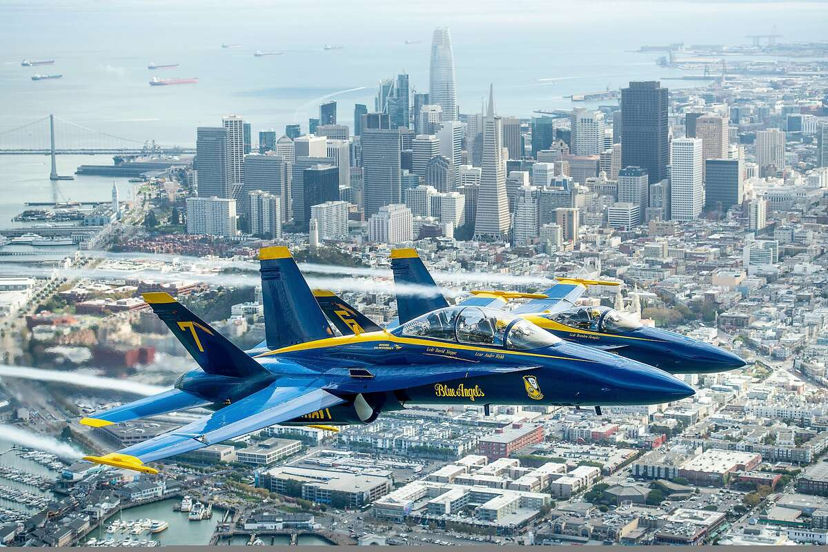 In advance of Fleet Week performances, the U.S. Navy Blue Angels and Team Oracle aerobatics pilot Sean D. Tucker fly over the San Francisco Bay during a photo flight on Thursday, Oct. 4, 2018. (AP Photo/Noah Berger)