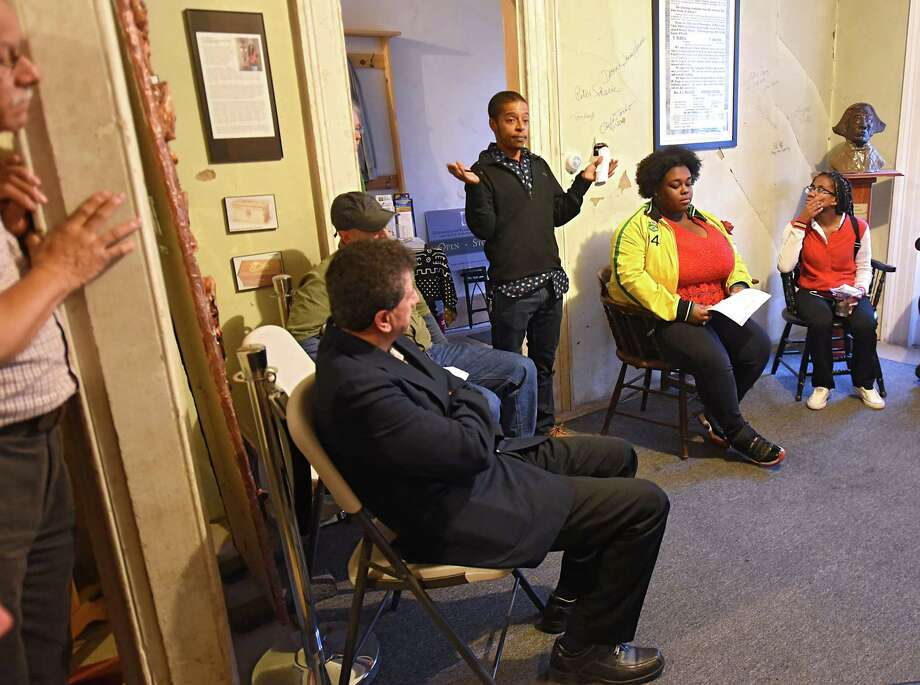 Artist Oliver Peters, third from right, talks about leading students to paint a timeline mural on the walls of the staircase in the Stephen and Harriet Myers Residence which is part of the Underground Railroad Heritage Trail on Livingston Ave. Thursday, Oct. 4, 2018 in Albany, N.Y. High school students applied for the chance to paint a mural along the staircase of the museum for the exhibit Seeking Sanctuary. The mural holds a timeline of events starting at 1741 with the Trans-Atlantic Slave Trade to the present day Black Live Matter movement and sanctuary cities. (Lori Van Buren/Times Union) Photo: Lori Van Buren, Albany Times Union / 20045024A