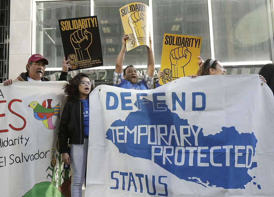 FILE - In this March 12, 2018 file photo, supporters of temporary protected status of immigrants cheer, hold signs and a banner with the outline of El Salvador at a rally at a federal courthouse in San Francisco, the day a lawsuit was filed against the Trump administration over its decision to end a program that lets immigrants live and work legally in the United States. During a hearing on Tuesday, Sept. 25, 2018, U.S. District Judge Edward Chen questioned the Trump administration's motives to end the program and repeated the president's vulgar language to describe some countries during a White House meeting in January. Chen is deciding whether to block the administration's decision to end temporary protected status for people from Sudan, Nicaragua, Haiti, and El Salvador. He did not immediately rule. (AP Photo/Jeff Chiu, File) Photo: Jeff Chiu / Associated Press