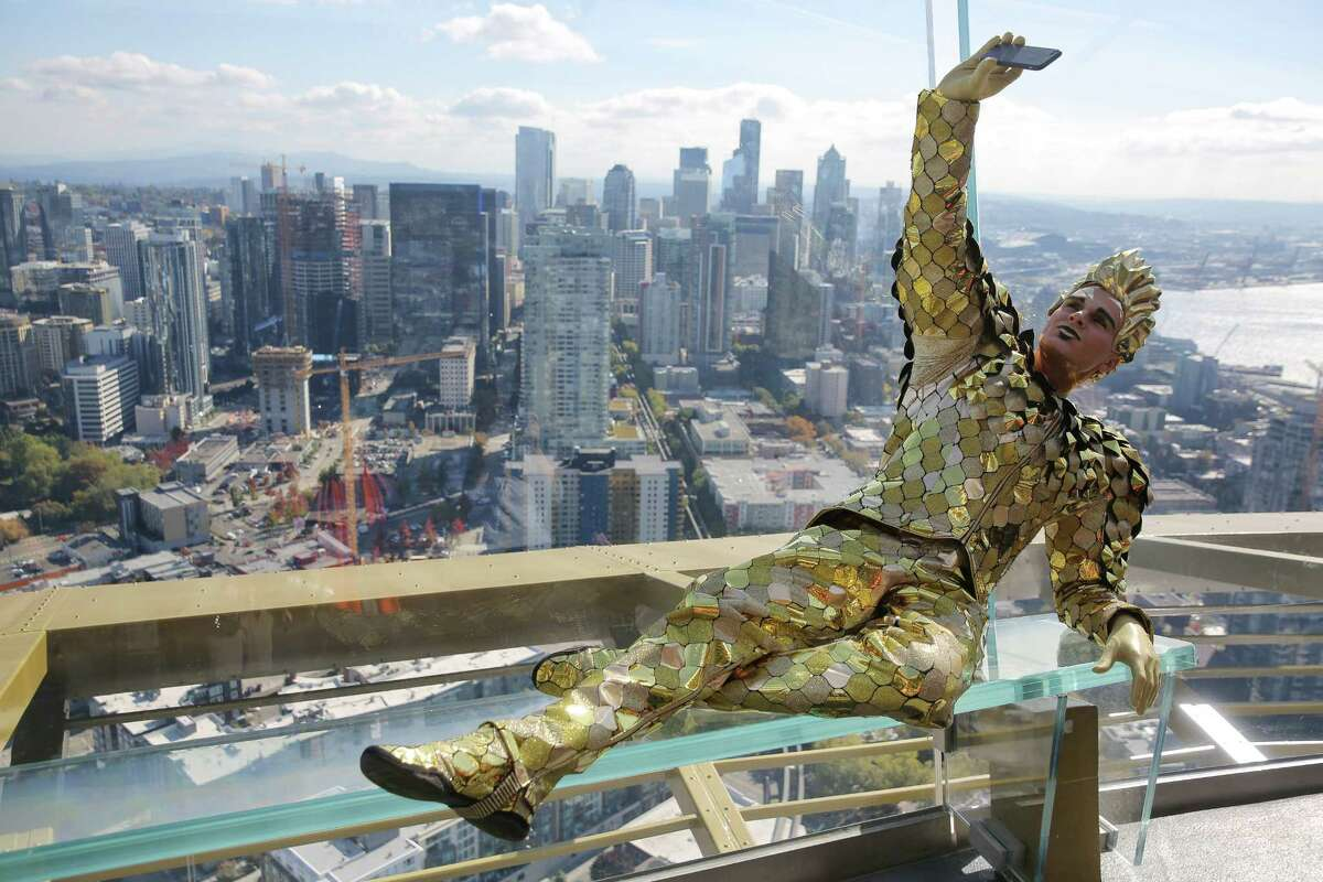 Andrey Kislitsin poses in his golden costume as he and other performers in Cirque du Soleil's VOLTA took over the Space Needle, Thursday, doing acrobatics and poses on the roof, antenna, observation deck and between the rotating glass floors, Oct. 4, 2018. VOLTA will be in Seattle for one more month before moving on to the next city.