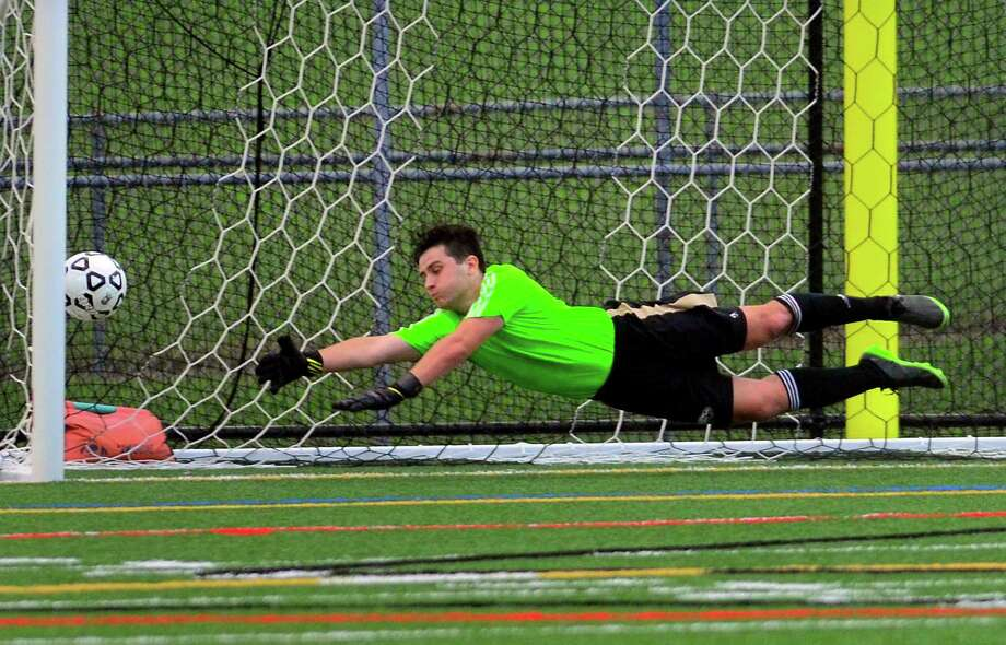 The ball kicked by Greenwich's Christopher Cruz gets past Trumbull goalie Christopher Prizio during boys soccer action in Trumbull on Thursday/ Photo: Christian Abraham / Hearst Connecticut Media / Connecticut Post