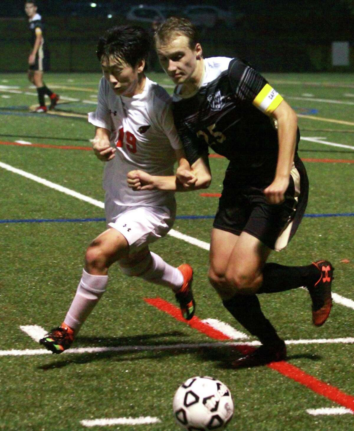 Greenwich's Woojin Kwak, left, and Trumbull's John Recker scramble for the ball during boys soccer action in Trumbull, Conn., on Thursday Oct. 4, 2018.