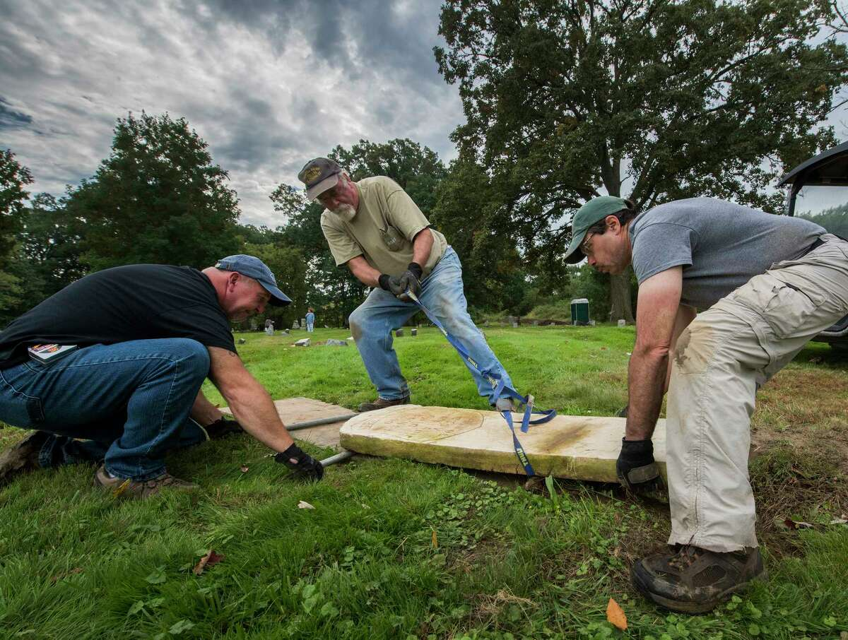 Volunteers Mark Bruno, left, Mike Cavanaugh, center and John Sasso, right, move a grave stone to its former site during the restoration at the St. Patrick's Cemetery as part of the Veterans Memorial Restoration Program that is going on at the cemetery Thursday Oct.4, 2018 in Watervliet, N.Y. (Skip Dickstein/Times Union)