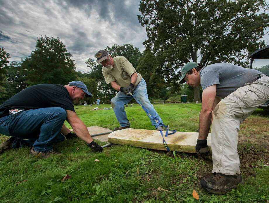 Volunteers Mark Bruno, left, Mike Cavanaugh, center and John Sasso, right, move a grave stone to its former site during the restoration at the St. Patrick's Cemetery as part of the Veterans Memorial Restoration Program that is going on at the cemetery Thursday Oct.4, 2018 in Watervliet, N.Y.  (Skip Dickstein/Times Union) Photo: SKIP DICKSTEIN / 200445012A