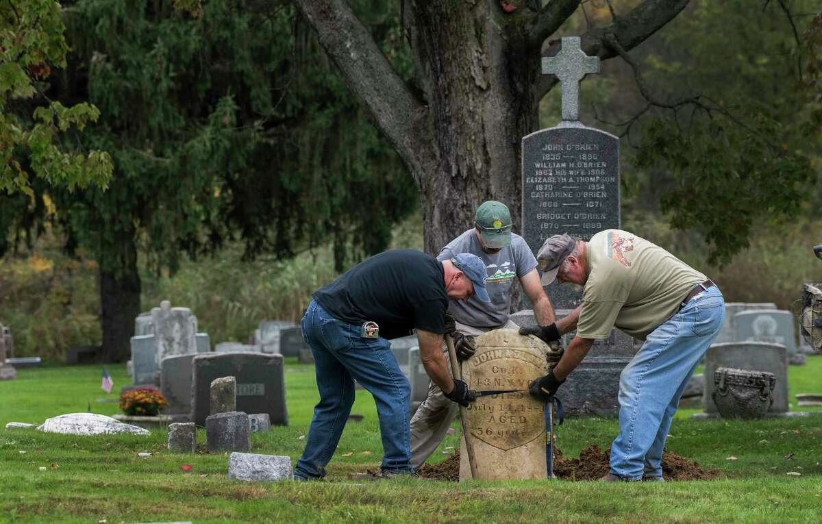 Volunteers Mark Bruno, left, John Sasso, center and Mike Cavanaugh move a grave stone in to place during their restoration at the St. Patrick's Cemetery as part of the Veterans Memorial Restoration Program that is going on at the cemetery Thursday Oct.4, 2018 in Watervliet, N.Y. (Skip Dickstein/Times Union)