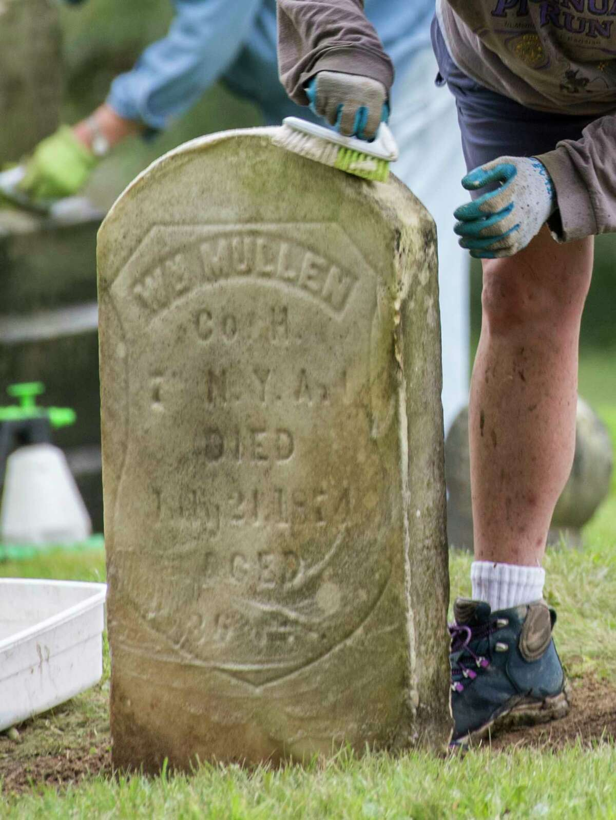 Volunteers Nancy Poulin, foreground and Chris Connell, background scrub grave stones during their restoration at the St. Patrick's Cemetery as part of the Veterans Memorial Restoration Program that is going on at the cemetery Thursday Oct.4, 2018 in Watervliet, N.Y. (Skip Dickstein/Times Union)