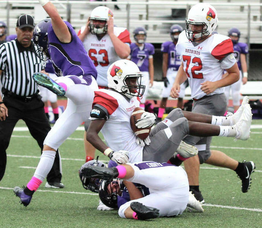 Alton's Terrance Walker (center) is taken down by a Collinsville defender after making a catch while Alton lineman Tristan Underwood (72) follows the play in a Redbirds' SWC win Sept. 8 in Collinsville. The Redbirds are back on the road Friday night for a SWC date at O'Fallon. Photo: Greg Shashack / The Telegraph