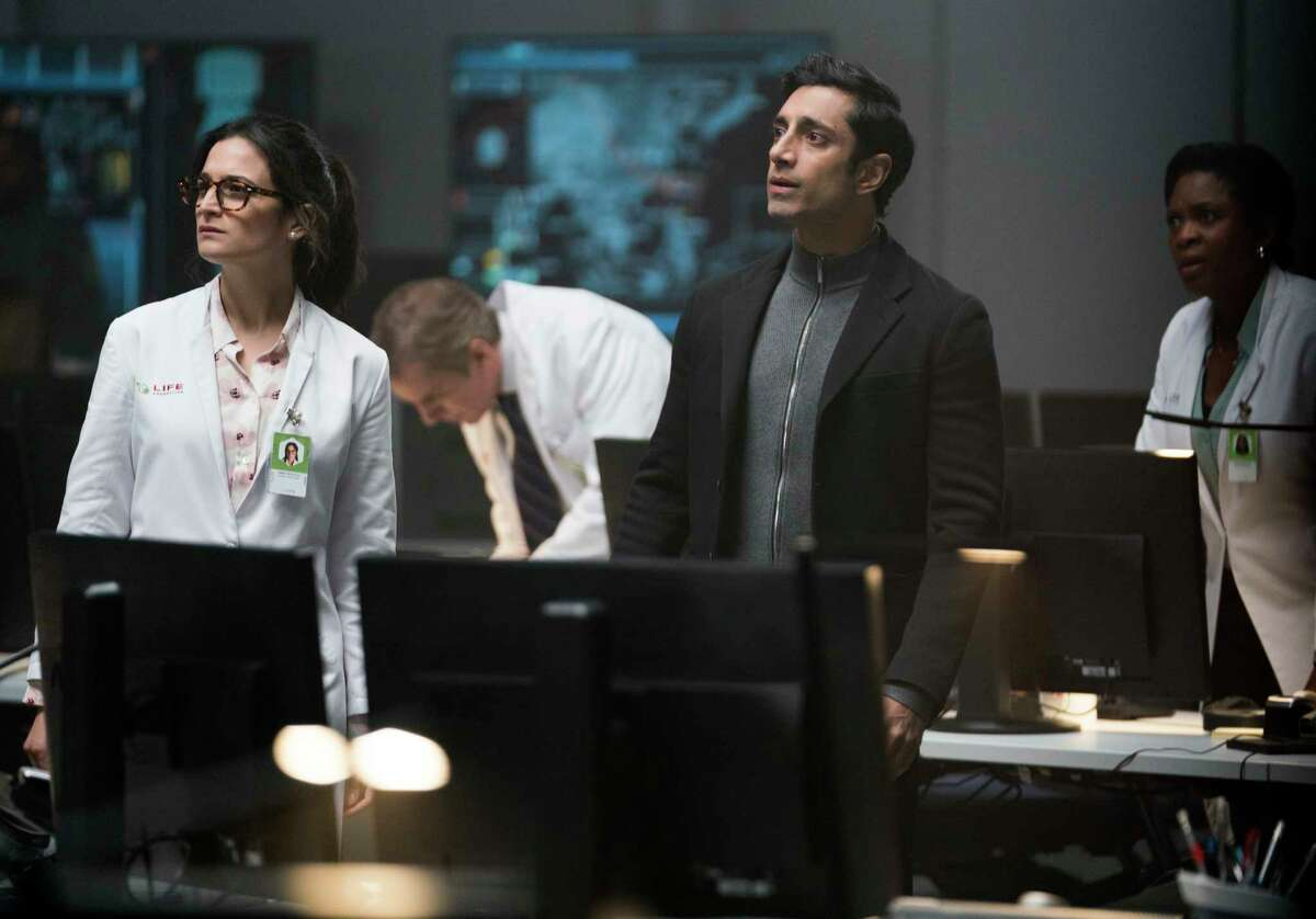 """This image released by Sony Pictures shows Jenny Slate, left, and Riz Ahmed in a scene from """"Venom."""" (Jessica Miglio/Sony Pictures via AP)"""