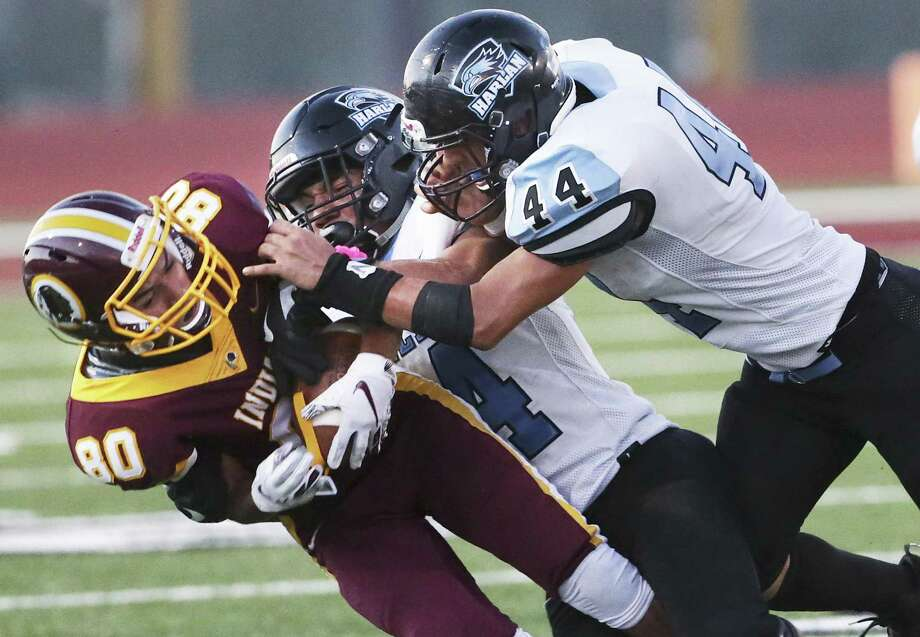 Indian receiver Joel Perez is slammed to the ground after a catch by Hawk defenders Samuel Carter and Manuel Leon (44) as Harlandale hosts Harlan at Harlandale Memorial Stadium on October 4, 2018. Photo: Tom Reel, Staff / Staff Photographer / 2017 SAN ANTONIO EXPRESS-NEWS