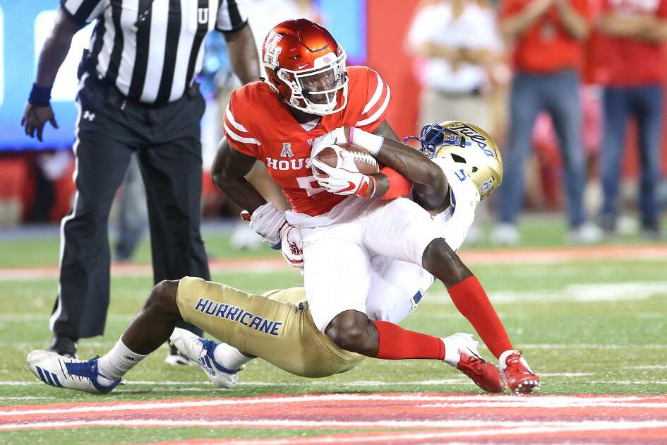 Houston Cougars wide receiver Marquez Stevenson (5) holds onto the ball as Tulsa Golden Hurricane safety McKinley Whitfield (5) tries to take him down in the first quarter at TDECU Stadium on Thursday, Oct. 4, 2018 in Houston.