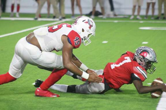 South Houston quarterback Torrence Stevens dives for a fumble in the opening minutes of Thursday night's game. With his arm around the ball, he appears to be recovering the ball but Atascocita's Asyrun Simon wound up with it. Two plays later, the Trojans were already losing 14-0.