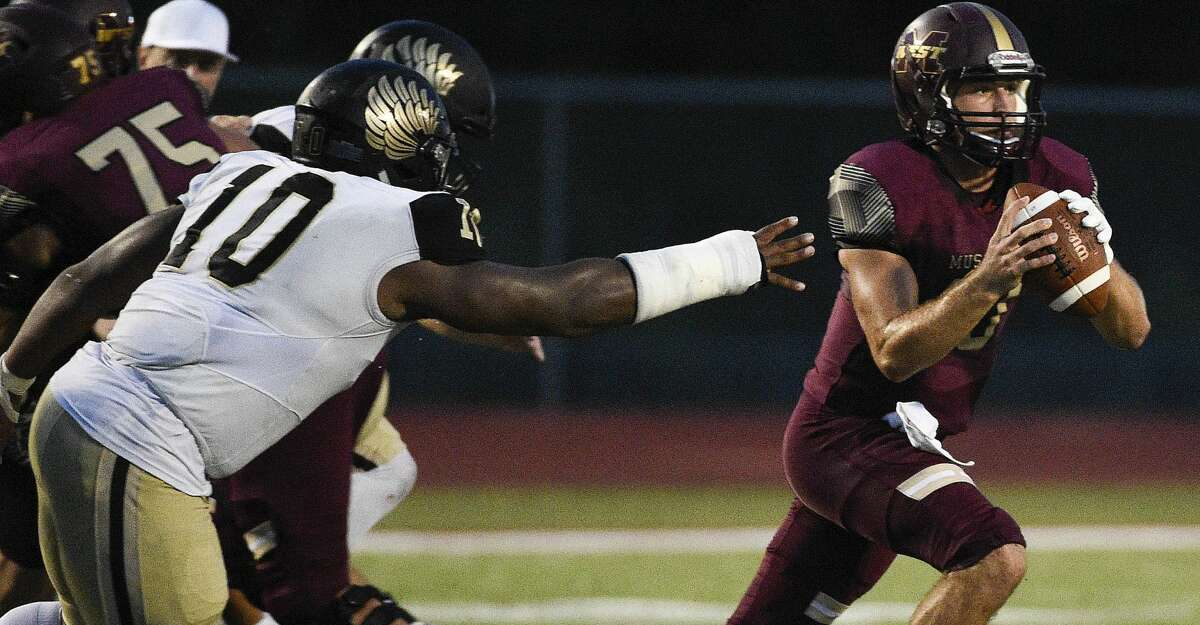 Magnolia West quarterback Jon Matocha, right, avoids the tackle of Foster defensive lineman Chidozie Nwankwo during the first half of a high school football game, Friday, Sept. 14, 2018, in Magnolia, TX. (Eric Christian Smith/Contributor)