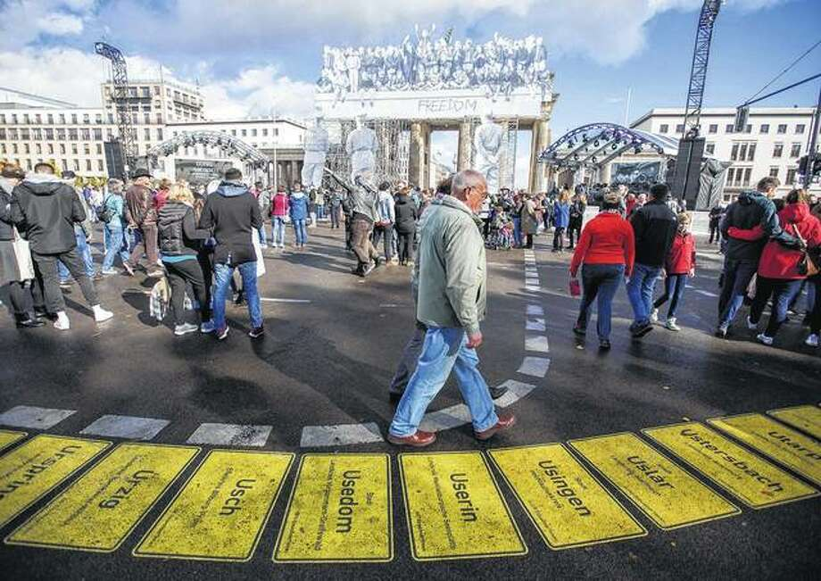 Visitors celebrate the Day of German Unity walk in front of the Brandenburg Gate on Wednesday. Photo: Jens Büttner | AFP (Getty Images)