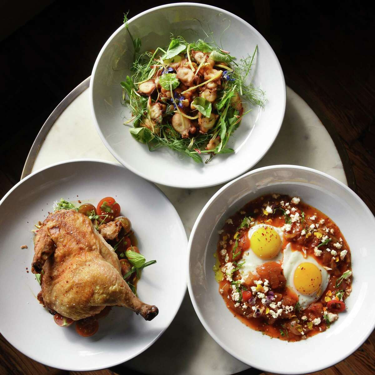 Octopus salad, top, roasted chicken and Shakshuka, right, at Le Perche restaurant on Warren Street Thursday Sept. 27, 2018 in Hudson, NY. (John Carl D'Annibale/Times Union)