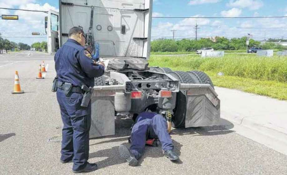 Two Laredo police officers check on a tractor-truck Thursday morning at the intersection of Mines and Rancho Viejo roads. LPD spent Wednesday and Thursday inspecting commercial motor vehicles. Police said having the vehicles in compliance can avoid accidents. Photo: Laredo Morning Times