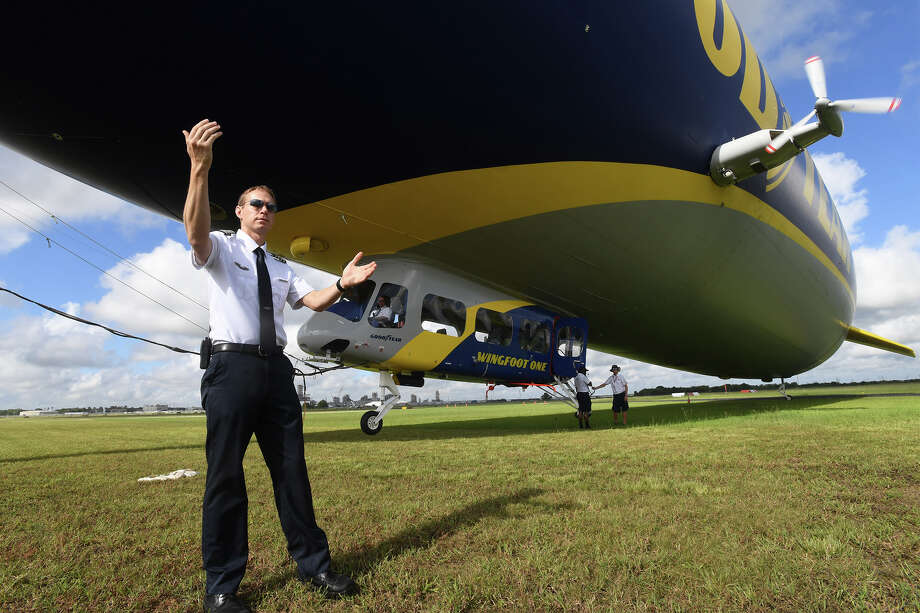 Assistant Chief Pilot Adam Basaran guides passengers towards a Goodyear blimp at the Beaumont Municipal Airport on Thursday. Using a raffle system, Goodyear will be giving 132 local employees an opportunity to ride the famed dirigible until Friday.   Photo taken Thursday, 10/4/18 Photo: Guiseppe Barranco/The Enterprise / Guiseppe Barranco ?