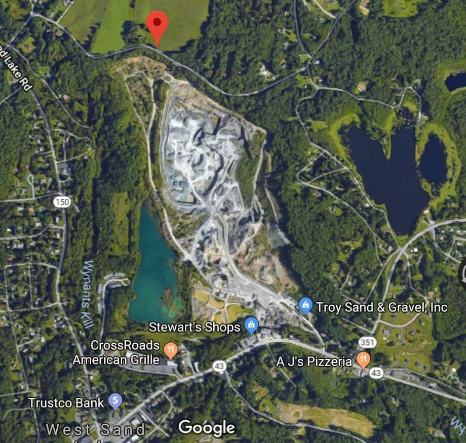 The Troy Sand & Gravel mine in West Sand Lake, where the owners paid a $5,000 state fine for improper mining off Stop 13 Road (below and to the left of the red arrow). Photo: Nearing, Brian, Google Maps