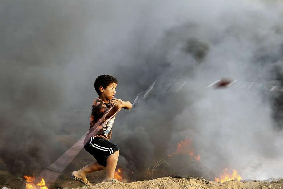A Palestinian boy reacts to tear gas fired by Israeli forces during clashes along the Gaza-Israel border in the Gaza Strip. The Israeli military said about 20,000 protesters participated. Photo: Said Khatib / AFP / Getty Images
