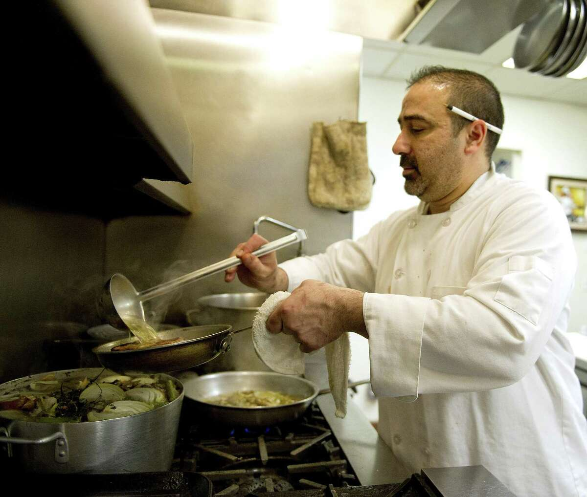 Stephen Costanzo, co-owner and head chef at Olio in Stamford, cooks in the kitchen.
