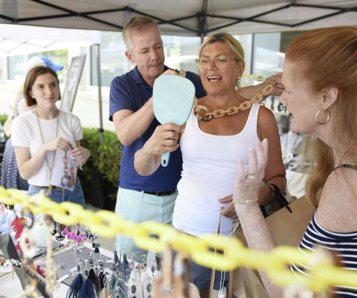 Rush Accessories owner Dennis Mathews helps Joan Arcoleo, of Rye, N.Y., try on a necklace during the 2018 Sidewalk Sale Days in downtown Greenwich, Conn. Thursday, July 12, 2018. Presented by the Greenwich Chamber of Commerce, more than 110 merchants marked down clothing, jewelry and accessories, attracting thousands of shoppers from near and far. The sidewalk sale continues Friday, Saturday and Sunday.