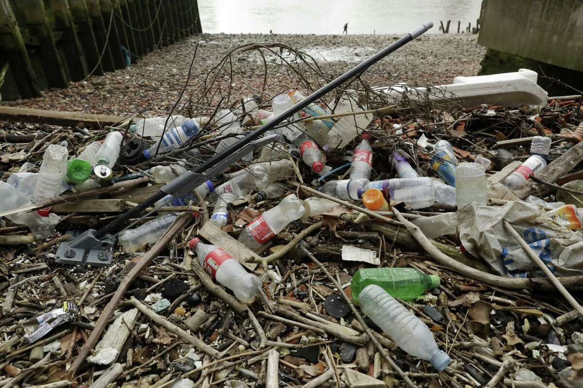 Plastic bottles and other plastics including a mop, lie washed up on shore.