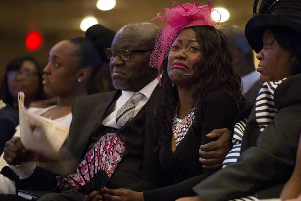 Roxane Freeman, center, grieves the loss of her husband, Heywood, and children, Halynn and Haywood Jr., during the funeral service at the Greater Grace Outreach Church.
