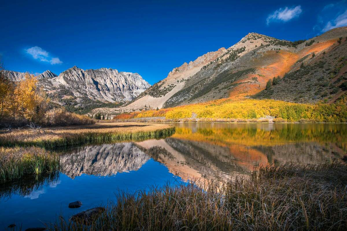 Brilliant fall colors usually peak first in the Easter Sierras, including along the North Lake of Bishop Creek Canyon with brilliant in the red and gold foliage.