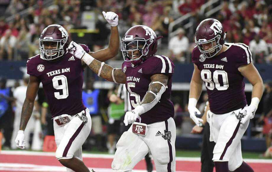 Texas A&M running back Trayveon Williams (5) celebrates his touchdown run against Arkansas with wide receiver Hezekiah Jones (9) and tight end Trevor Wood (80) during the fourth quarter of an NCAA college football game Saturday, Sept. 29, 2018, in Arlington, Texas. (AP Photo/Jeffrey McWhorter) Photo: Jeffrey McWhorter, FRE / Associated Press / Copyright 2018 The Associated Press. All rights reserved
