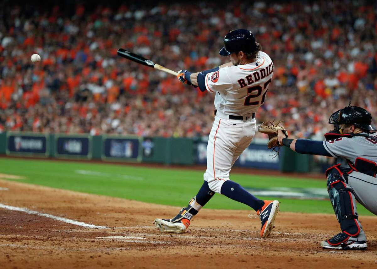 Houston Astros outfielder Josh Reddick (22) hits an RBI single to right field scoring Houston Astros first baseman Yuli Gurriel (10) off Cleveland Indians pitcher Corey Kluber (28) in the fourth inning of Game 1 of the American League Division Series at Minute Maid Park on Friday, Oct. 5, 2018, in Houston.
