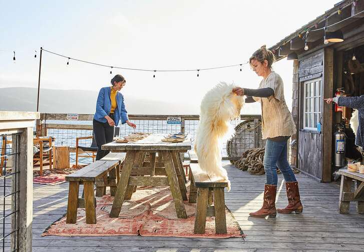 Kelli Dunaj (left) of Spring Coyote Ranch adds one of her sheepskins to the bench before a West Marin makers dinner at the boat house at Nick�s Cove on Tomales Bay on Thursday, Sept. 13, 2018 in Marshall, CA. The makers all know each other and contributed something from their craft to the meal.