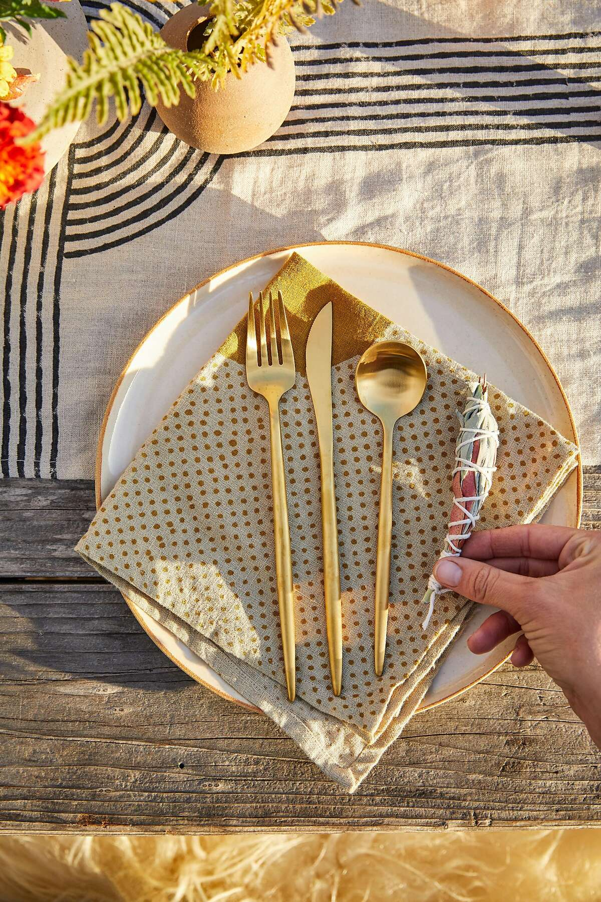 Heather Frye of Venn Floral adds smudge sticks to the table before a West Marin makers dinner at the boat house at Nick�s Cove on Tomales Bay on Thursday, Sept. 13, 2018 in Marshall, CA. The makers all know each other and contributed something from their craft to the meal.