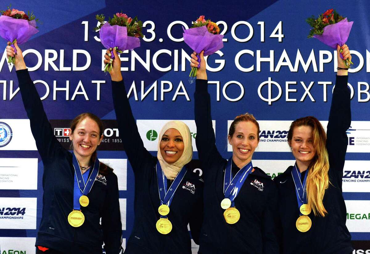 (From L) Anne-Elisabeth Stone, Ibtihaj Muhammad, Mariel Zagunis and Dagmara Wozniak of the United States team celebrate with their medals on the podium after winning the women's team sabre final at the 2014 World Fencing Championships in Kazan, on July 21, 2014. AFP PHOTO / VASILY MAXIMOVVASILY MAXIMOV/AFP/Getty Images ORG XMIT: -