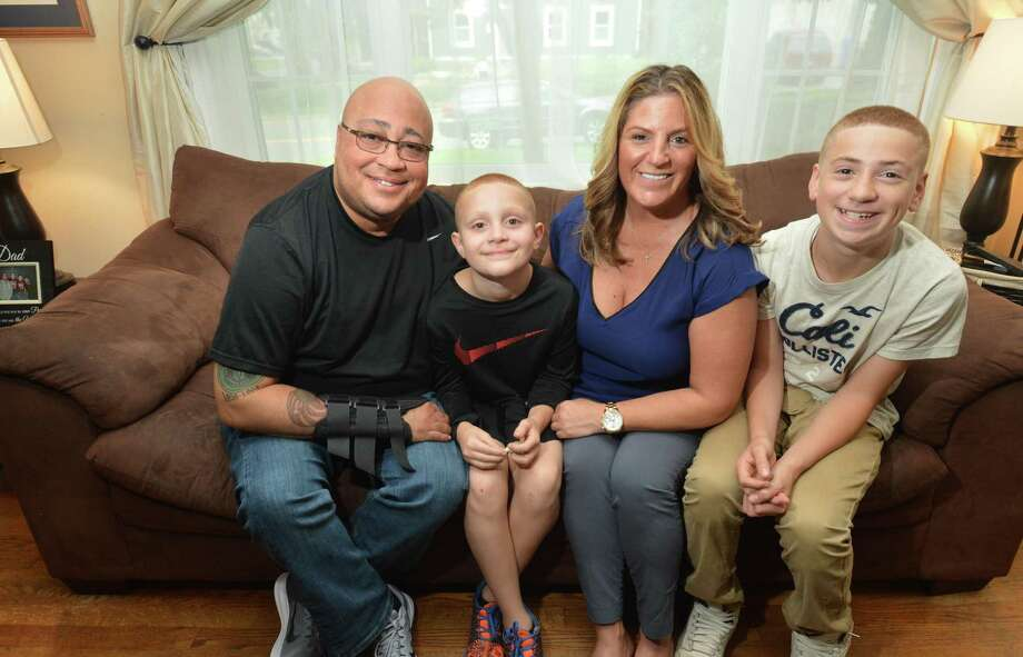 Patrolman Phil Roselle, at his Norwalk home in September with his wife Debbie and two of his sons, 9-year-old Ryan and 14 year-old Michael. Photo: Alex Von Kleydorff / Hearst Connecticut Media / Norwalk Hour