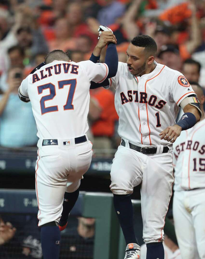 Houston Astros shortstop Carlos Correa (1) and Houston Astros second baseman Jose Altuve (27) celebrate in the fifth inning of Game 1 of the American League Division Series at Minute Maid Park on Friday, Oct. 5, 2018, in Houston.