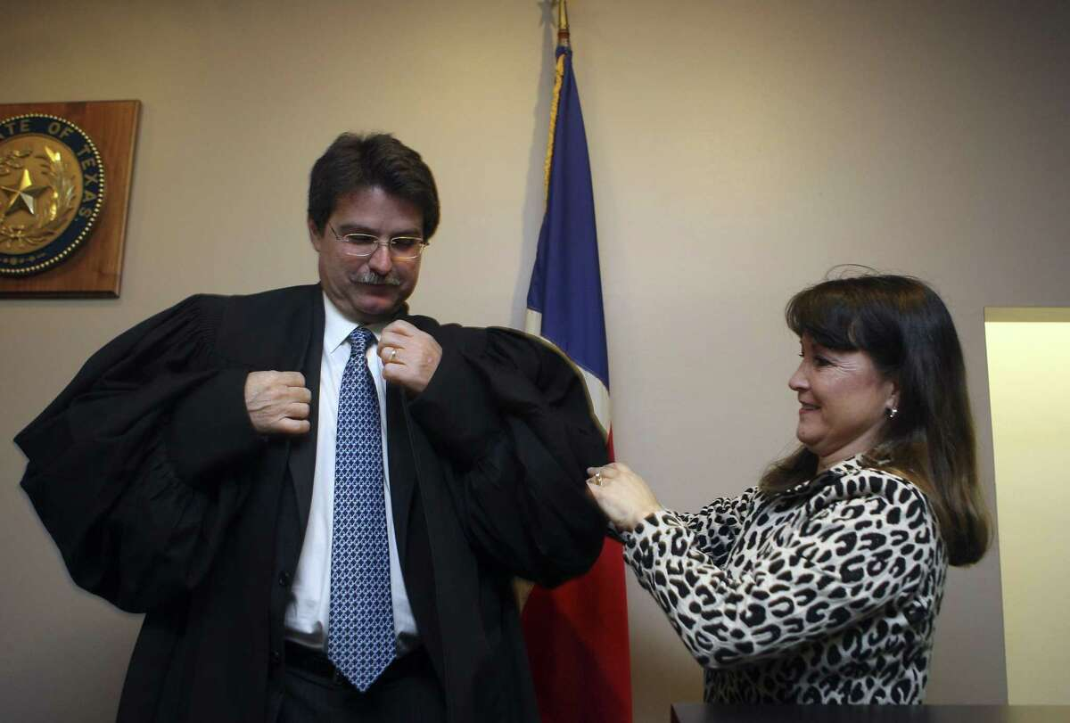 Walden Shelton, Jr. gets some help with his new robe from his wife Michelle Shelton after being sworn in as judge of the County Court at Law No. 9 on January 1, 2011. Shelton is among the Editorial Board picks for seats in the November election.