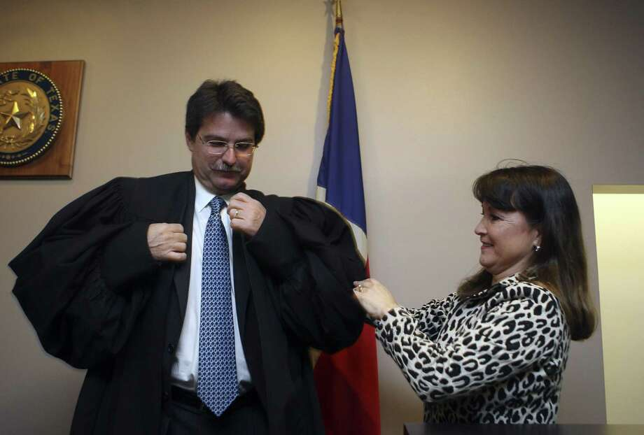 Walden Shelton, Jr. gets some help with his new robe from his wife Michelle Shelton after being sworn in as judge of the County Court at Law No. 9 on January 1, 2011. Shelton is among the Editorial Board picks for seats in the November election. Photo: HELEN L. MONTOYA /SAN ANTONIO EXPRESS-NEWS / hmontoya@express-news.net